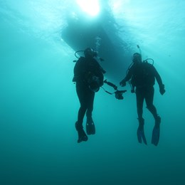 Two divers deep underwater